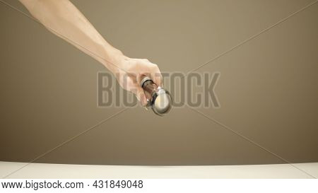 Caucasian Male Hand Holds A Flashlight And Fails To Switch In On On A Brown Wall Background. Action.