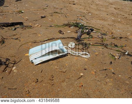 A Used Medical Mask Was Left On A Sandy Beach. A Dented Blue Face Shield On The Sand. Pandemic Coron