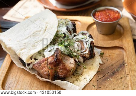Portion Of Juicy Kebabs With Onions On A Wooden Tray With Pita Bread And Sauce