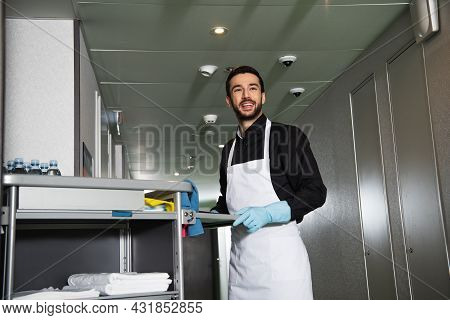 Cheerful And Bearded Housekeeper In Rubber Gloves Standing Near Cart In Corridor Of Hotel