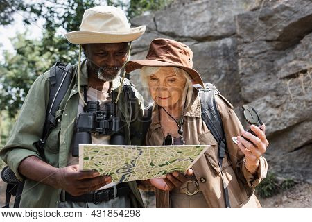 Multiethnic Couple Of Hikers With Compass Looking At Map In Forest.