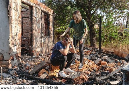 Young Couple On The Ruins Of House Destroyed With Fire. Damaged Window, Walls And Floor, Burnt Woode