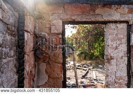 House Destroyed With The Fire. Missing Window, Damaged Gas Meter, Burnt Wooden Frame, Cracked Walls,