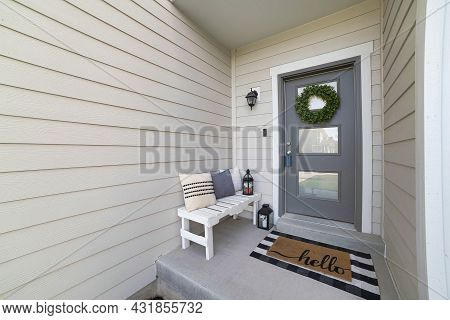 Small Front Porch With White Bench And Gray Front Door