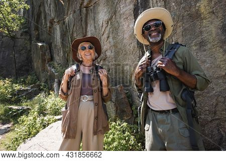 Positive Multiethnic Couple With Binoculars And Backpacks Standing Near Cliff.
