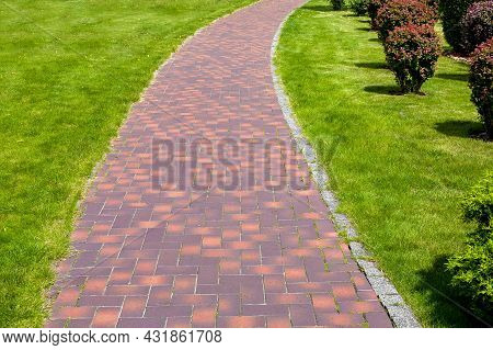 Curved Stone Tile Pavement Crescent, Path In Park Landscaped With Green Grass And Bushes, Garden Lan