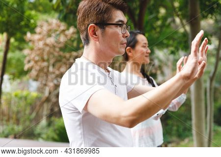 Asian couple wearing white shirts exercising outdoors, practicing tai chi. family fitness time in garden.
