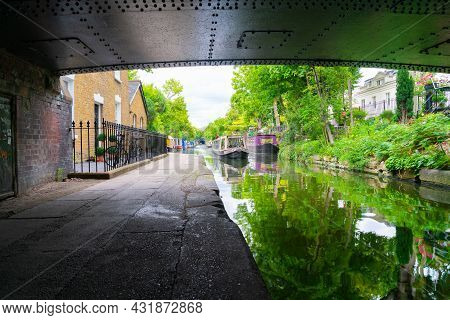London - England - August 5 2017; From Under A Bridge Looking Into The Day Narrow Boats And Canal Ac