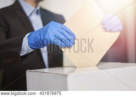 A Person In Medical Gloves Voting. Election Concept. Presidential Or Parliament Election. A Voter Pu