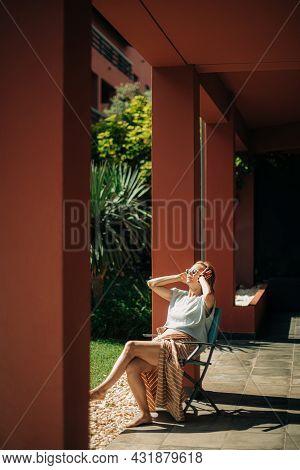 Pretty Mid Adult Woman Resting On Veranda Outdoors. Lady Wearing Sunglasses Sitting Barefoot On Chai