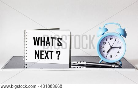 Question What's Next Written On A Notebook Next To A Clock And A Pen On A White And Black Background