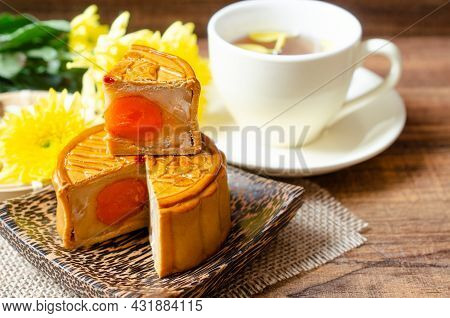 Closed Up Delicious Homemade Moon Cake On Wooden Plate Over Blur Tea Cup And Chrysanthemum Flower. F