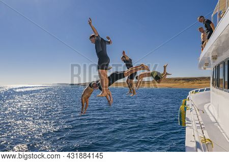 Sharm El Sheikh, Egypt - 23 Dec 2019: Fly After Jump. Men's Group Jumping From Yacht Into Blue Sea W