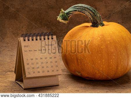 October 2021 - spiral desktop calendar with a pumpkin, time and business concept