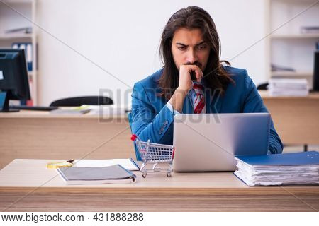 Young male employee in ecommerce concept in the office