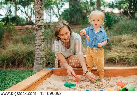 Mother And Child Playing With Sand In Sandbox. Portrait Of Happy Mid Adult Woman Spending Time With