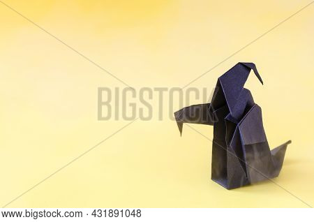 The Figure Of A Dark Ghost On A Yellow Background Is A Place For Text. A Dark Paper Ghost For The Ha