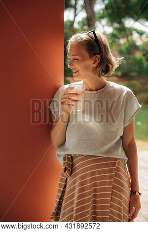 Portrait Of Positive Woman With Glass Of Water. Mid Adult Woman Standing At Wall, Drinking And Smili