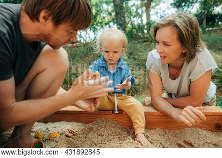 Mid Adult Parents Playing With Child In Sandbox. Cute Toddler Girl Sitting In Sandpit, Man And Woman