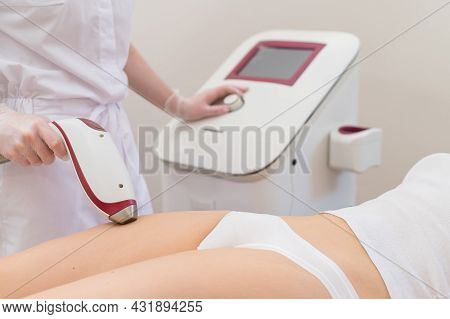 A Woman In A Professional Beauty Salon Removes Unwanted Vegetation In The Bikini Area Using Laser Ha