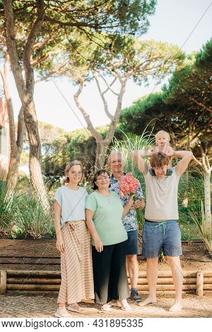 Portrait Of Happy Family With Little Child. Mid Adult Couple With Grandparents And Toddler Daughter