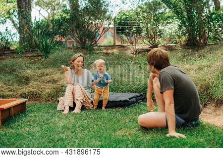 Happy Family With Little Child Resting On Backyard. Woman Sitting With Daughter On Mattress And Look
