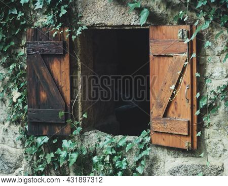 Wooden Windows Of An Old Mill Surrounded By Leaves