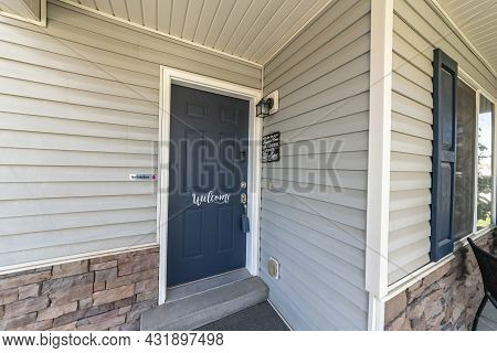 Blue Front Door Of A House With White Welcome Calligraphy At The Front
