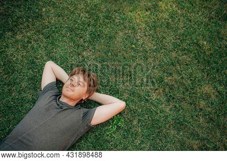 Portrait Of Serene Mid Adult Man Lying On Grass. Man Resting In Summer Outdoors. Copy Space. Relaxat