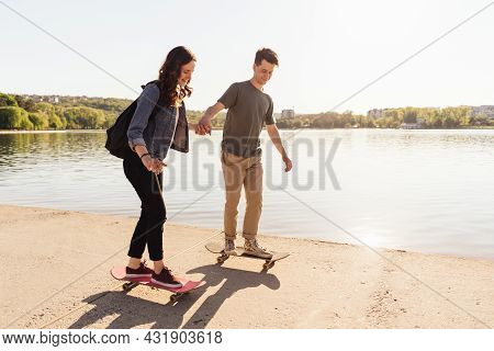 Young Caucasian Couple Teaching To Each Others While Practicing Skating, Lifestyle Extreme Outdoor A