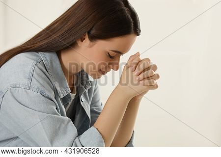 Religious Young Woman With Clasped Hands Praying Indoors, Closeup