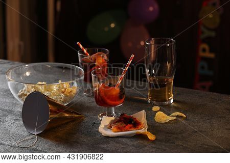 Messy Table With Drinks And Food Leftovers Indoors. After Party Chaos