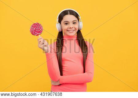 Amazed Girl Hold Lollipop Listen Music. Lollipop Child. Kid In Headphones Hold Lollypop.