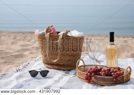 Bag, Blanket, Wine And Other Stuff For Beach Picnic On Sandy Seashore