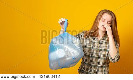 Banner Copy Space. Woman Holding A Smelly Garbage Bag On Yellow Background. Waste Sorting And Sustai