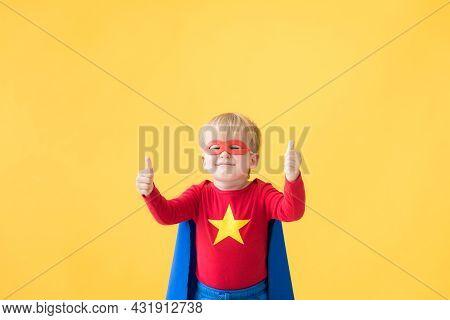 Superhero Child Against Yellow Paper Backdrop