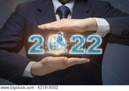 Businessman Start Up Business In 2022. Business Man Hold World Map And 2022 Show Happy New Year 2022