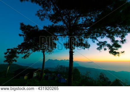 Colorful Sky At The Morning Over Mountains In North Of Thailand With Tents And House At Top Of Mount