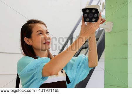 Beautiful Woman House Adjusts Direction Angle View Of Cctv Home Security Camera And Fine-tune Intern