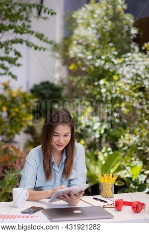 Businesswoman Sitting At Working Desk Using Tablet And Laptop Computer Connect To Internet In Small