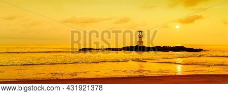 Panorama View Of Lighthouse On Small Rock Island With Orange Sky And Dramatic Clouds At Sunset. Take