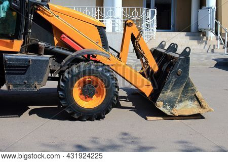 The Front Part Of Wheel Loader Bulldozer With Dirty Bucket On Repair Site In Town By Building. Sunny