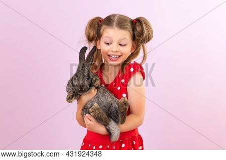 A Child Is Holding A Small Rabbit In His Hands. A Girl With A Rabbit On An Isolated Background.