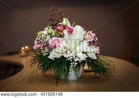 Designer Floral Table Arrangement Of Roses, Freesias And Decorative Materials In A Round Glass Bowl.