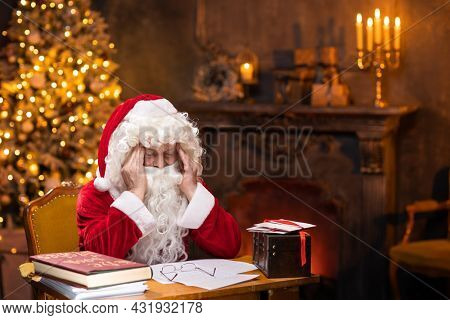 Workplace of Santa Claus. Tired and depressed Santa is sitting at the table. Fireplace and Christmas Tree in the background. Christmas concept.