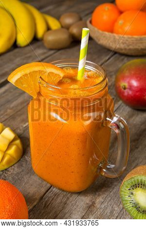 Mango, Orange, Banana And Kiwi Smoothie In A Glass Jar With Ingredients On A Old Wooden Table. Selec