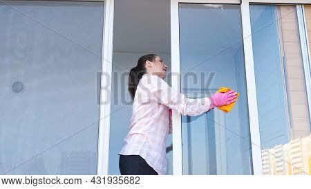 Brunette Woman In Gloves With Spray And A Rag Washes The Window, Outside View.