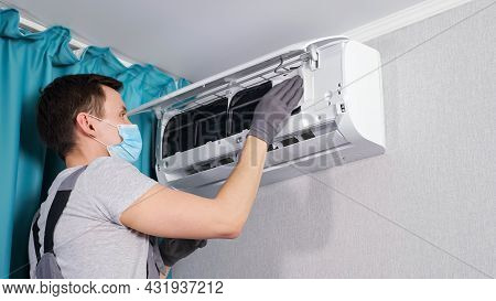 Concentrated Electrician In T-shirt And Face Mask Cleans Ceiling Air Conditioner Unit With White Clo