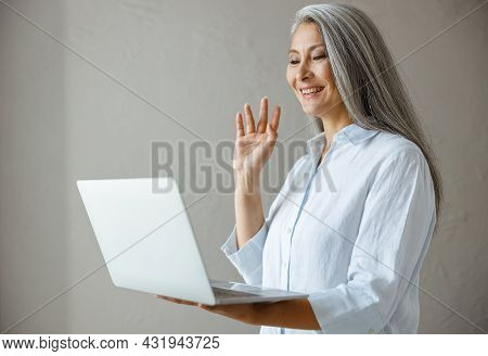 Smiling Hoary Haired Mature Asian Businesswoman Waves Hand At Videocall Via Laptop In Studio