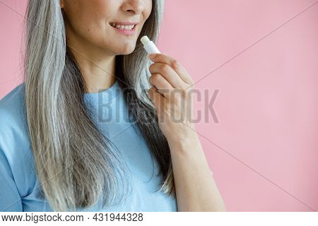 Middle Aged Woman Applies Lip Balm On Pink Background In Studio